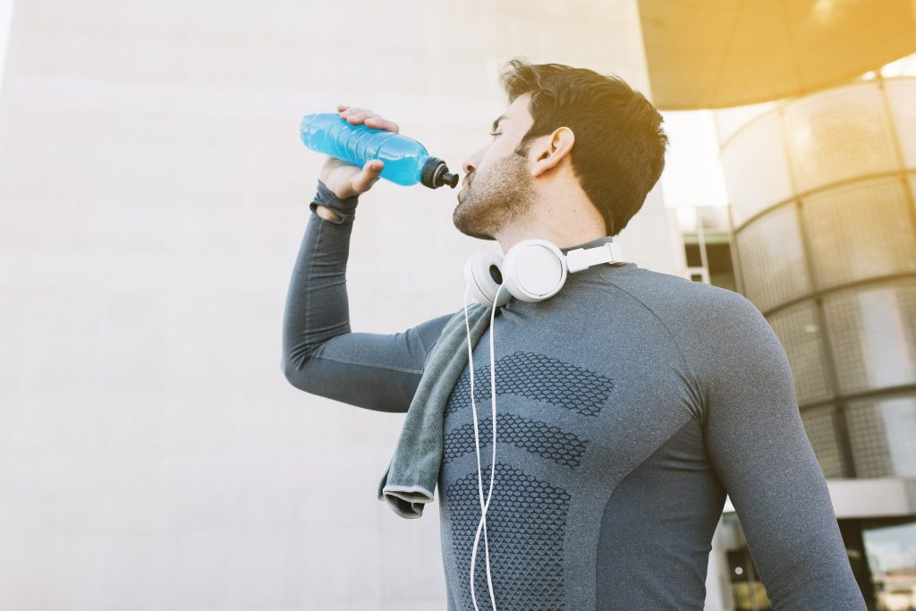 a man drinking water from a bottle during workouts