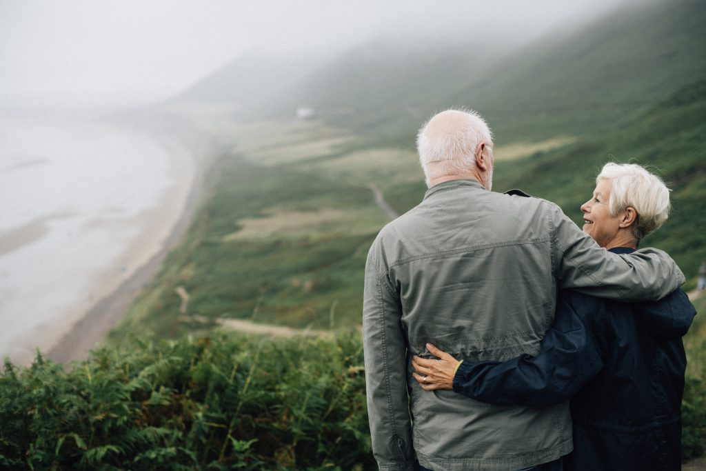 a elder couple looking at each other on the side of coastal ocean views