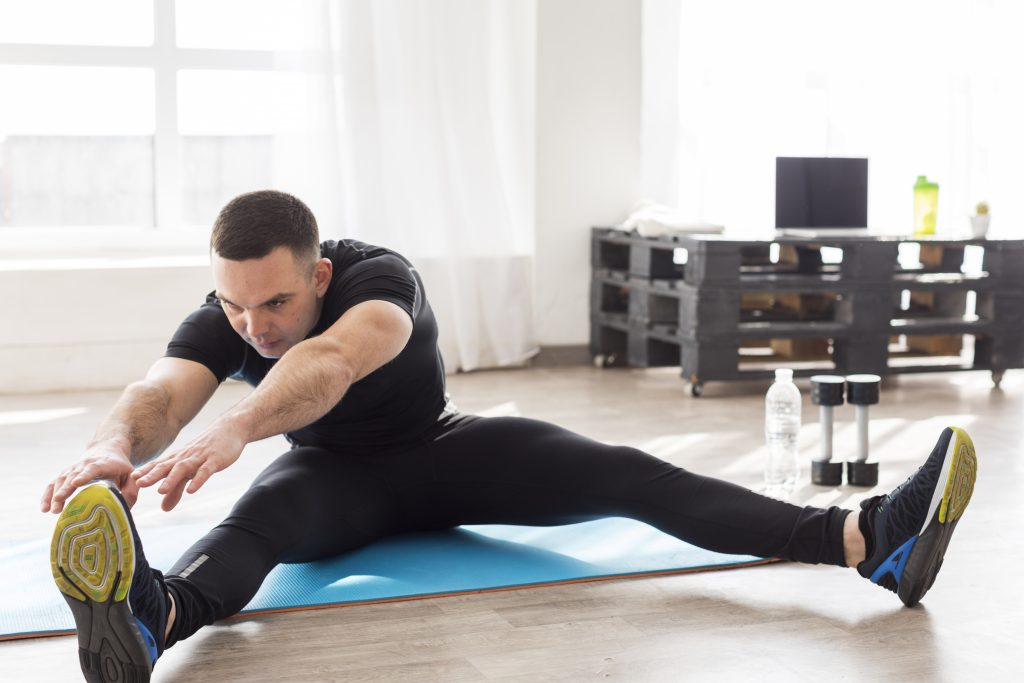 a man sitting inside a studio doing leg stretches