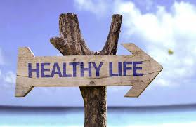 healthy life wooden sign next to the ocean pointing right