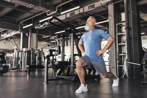 a man doing lunges in a gym environment
