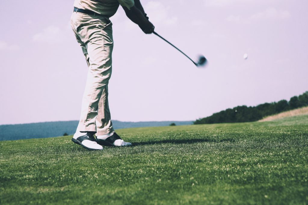 a man with golf club swinging in motion