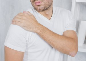 a man in chronic shoulder pain reaching for his right shoulder