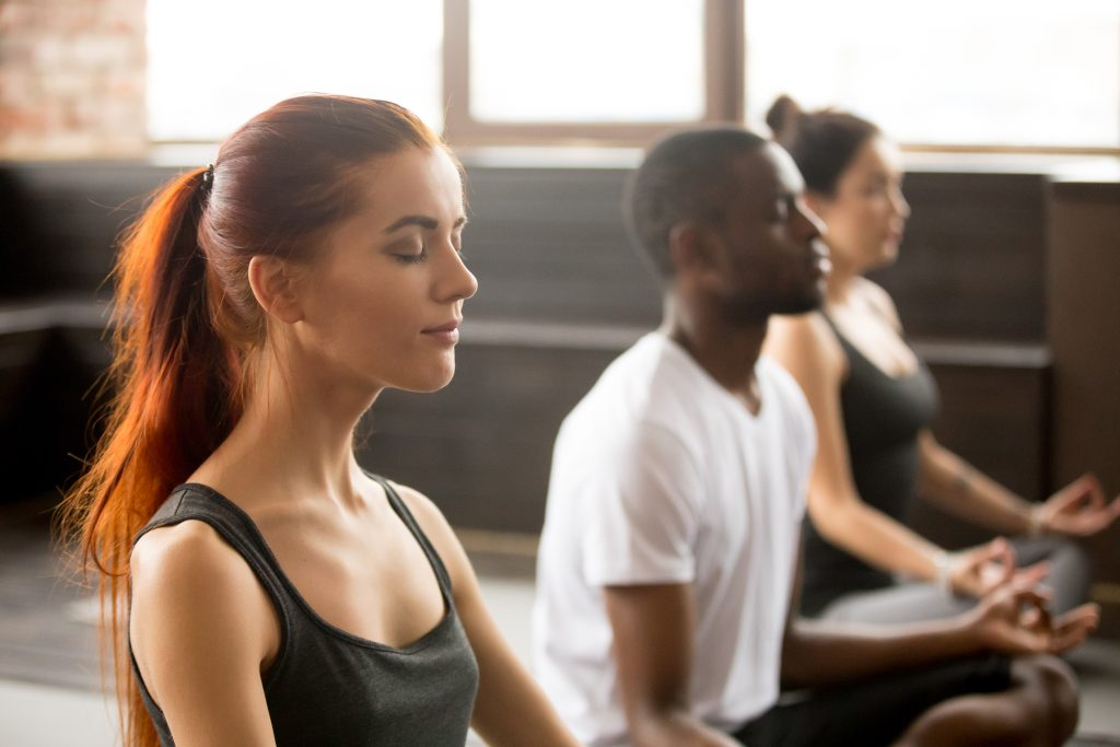three people meditating in a yoga studio