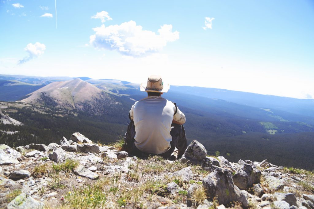 a man on top of a mountain looking out