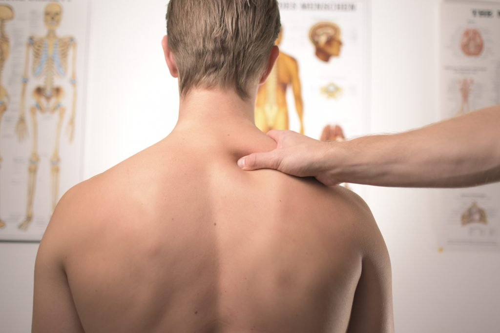 a man's back with doctor's hand pressing on back pain